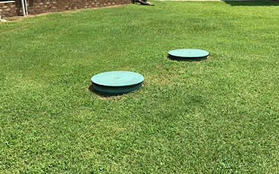 Two round plastic risers approximately two feet in diameter are installed in the lawn area to provide access to the septic tank